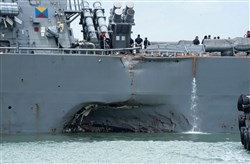 Damage to the portside is visible as the Guided-missile destroyer USS John S. McCain (DDG 56) steers towards Changi naval base in Singapore following a collision with the merchant vessel Alnic MC Monday.