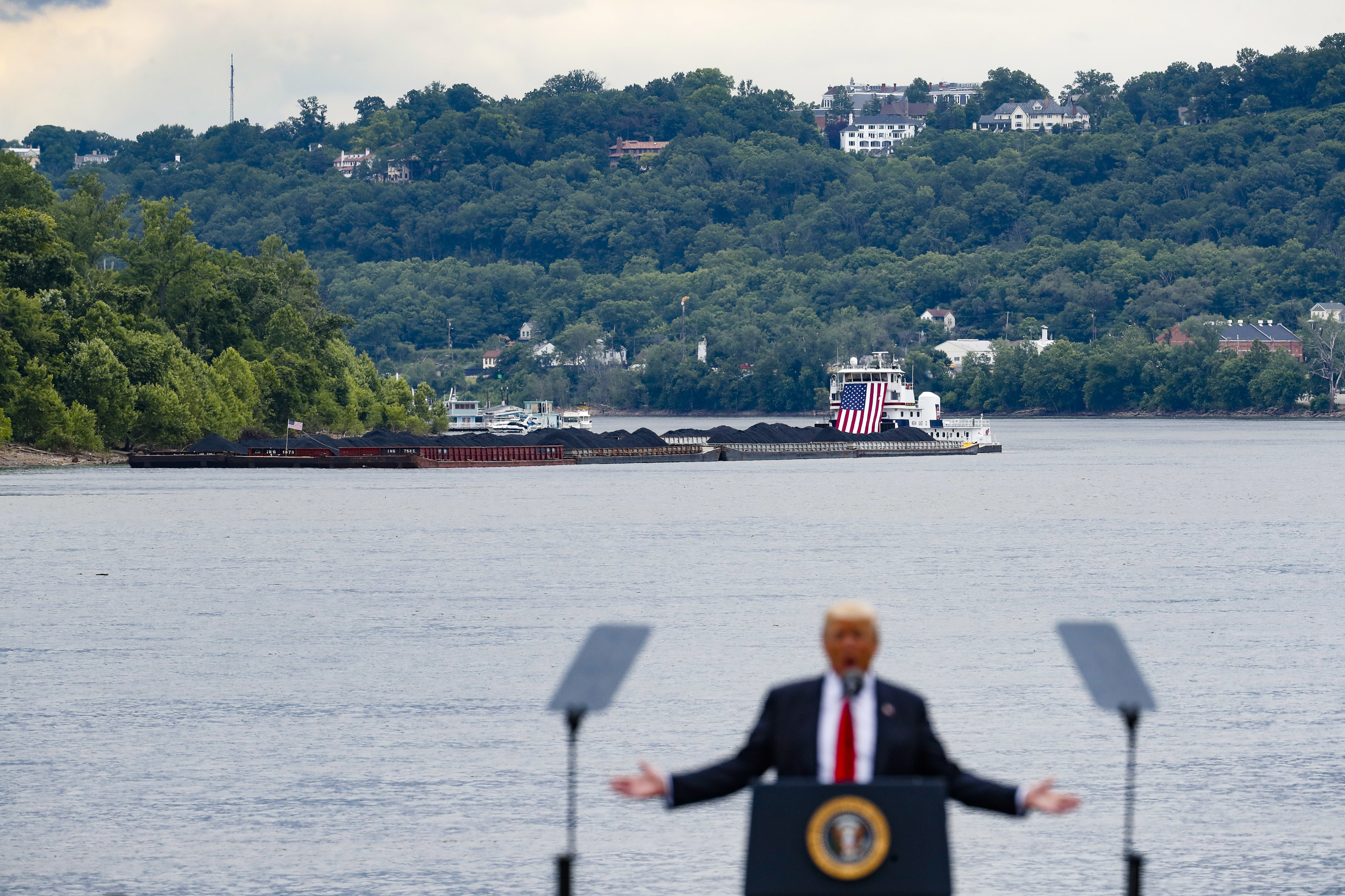 Trump Coal Plants FILE - In this June 7, 2017 file photo, a coal barge is positioned as a backdrop behind President Donald Trump as he speaks during a rally at the Rivertowne Marina in Cincinnati. President Donald Trump personally promised to activate emergency legal authorities to keep dirty or economically uncompetitive coal plants from shutting down, a top American coal company said. The Trump administration now says it has no plans to do so. (AP Photo/John Minchillo, File)