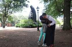 "Mayor Mike Signer hugs lifelong resident Aaliyah Jones in front of the newly covered statue of Thomas Jonathan ""Stonewall"" Jackson that stands in Justice Park, formerly known as Jackson Park, on Wednesday in Charlottesville, Va."
