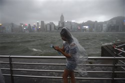 A woman uses her phone while wearing a plastic poncho along Victoria Harbour during heavy winds and rain brought on by Typhoon Hato in Hong Kong on Wednesday.