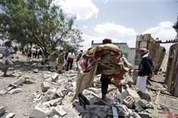 A Yemeni man carries his belongings at the site of an air raid Wednesday in the Arhab area of Yemen, where a Saudi-lead coalition has been bombing Iran-backed Houthi rebels.