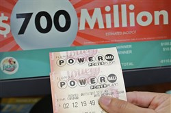A customer shows her purchased Powerball tickets for Wednesday's drawing in Hialeah, Fla.