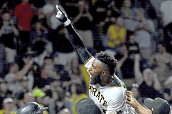 Pirates second baseman Josh Harrison is hoisted by teammates after hitting a walk-off home run against the Dodgers in the 10th inning Wednesday at PNC Park. Harrison's home run ended Rich Hill's no-hitter and gave the Pirates a walk-off victory.