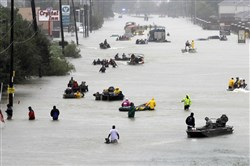 Rescue boats fill a flooded street as flood victims are evacuated as floodwaters from Harvey rise Monday in Houston.