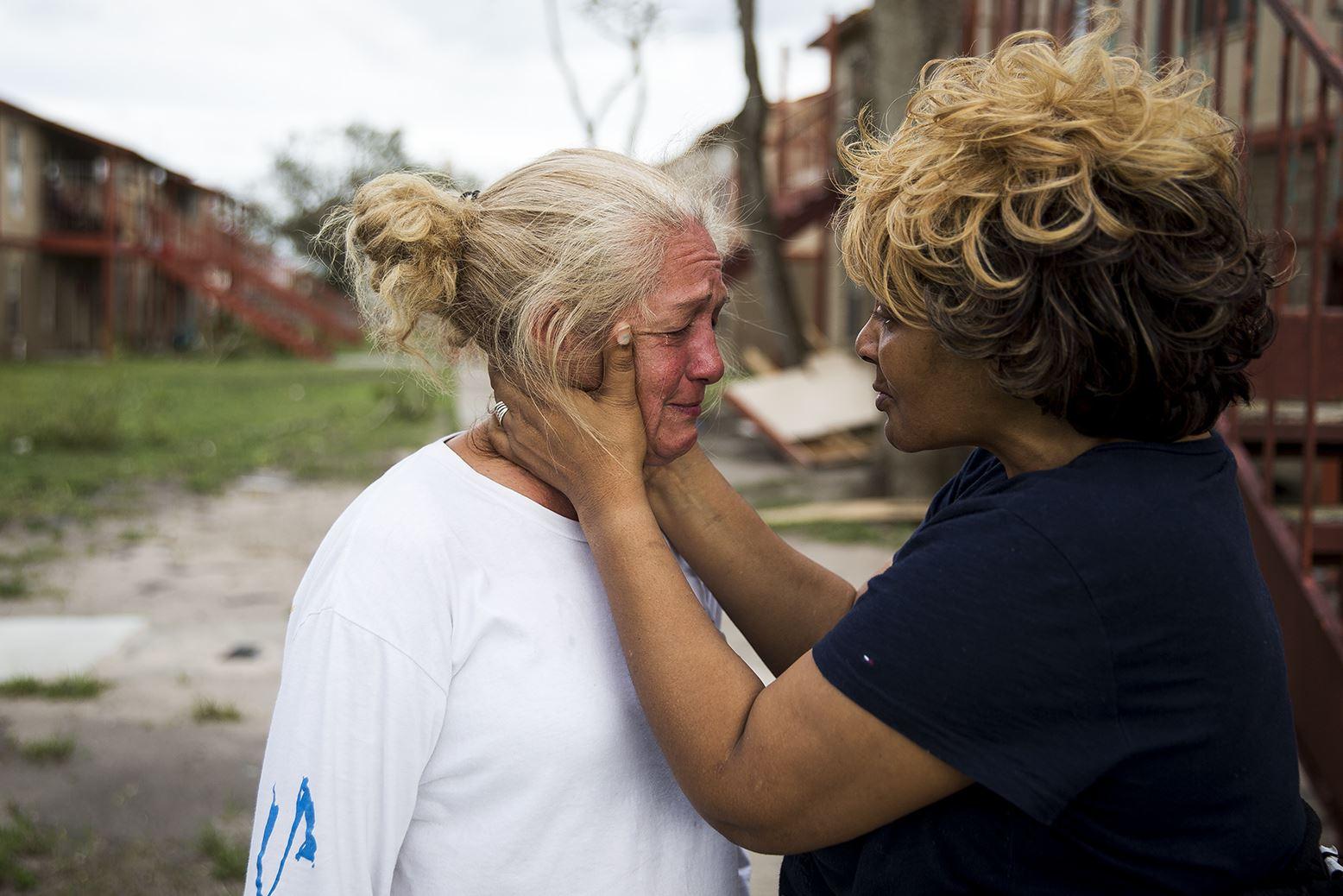 "APTOPIX Harvey-2 Genice Gipson comforts her lifelong friend, Loretta Capistran, outside of Capistran's apartment complex in Refugio, Texas, on Monday. ""We got to be strong, baby,"" Gipson told Capistran."