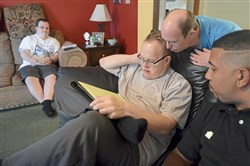 Matthew Mittelmeier, center, 49, prepares the weekly meal plan with input from housemates Jason Tessling, left, 34, and David Petrucco, second from right, 48, along with  Jovan Harris, a senior direct support specialist with Emmaus Community of Pittsburgh at a group home in Mt. Lebanon in August.