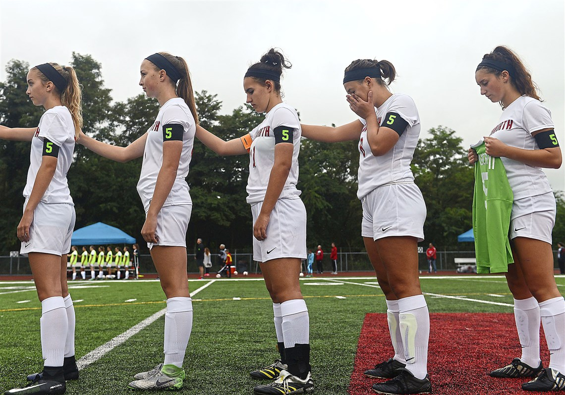 Avonworth players, from left, Hannah Miller, Jessica Lamperski, Devyn Hundertmark, Elizabeth Padalino and Bethany Kuyawinski stand for the national anthem after pausing for a moment of silence honoring teammate Hannah Milbert. The team wore armbands with the jersey number of Milbert, who was killed in a house fire in January.