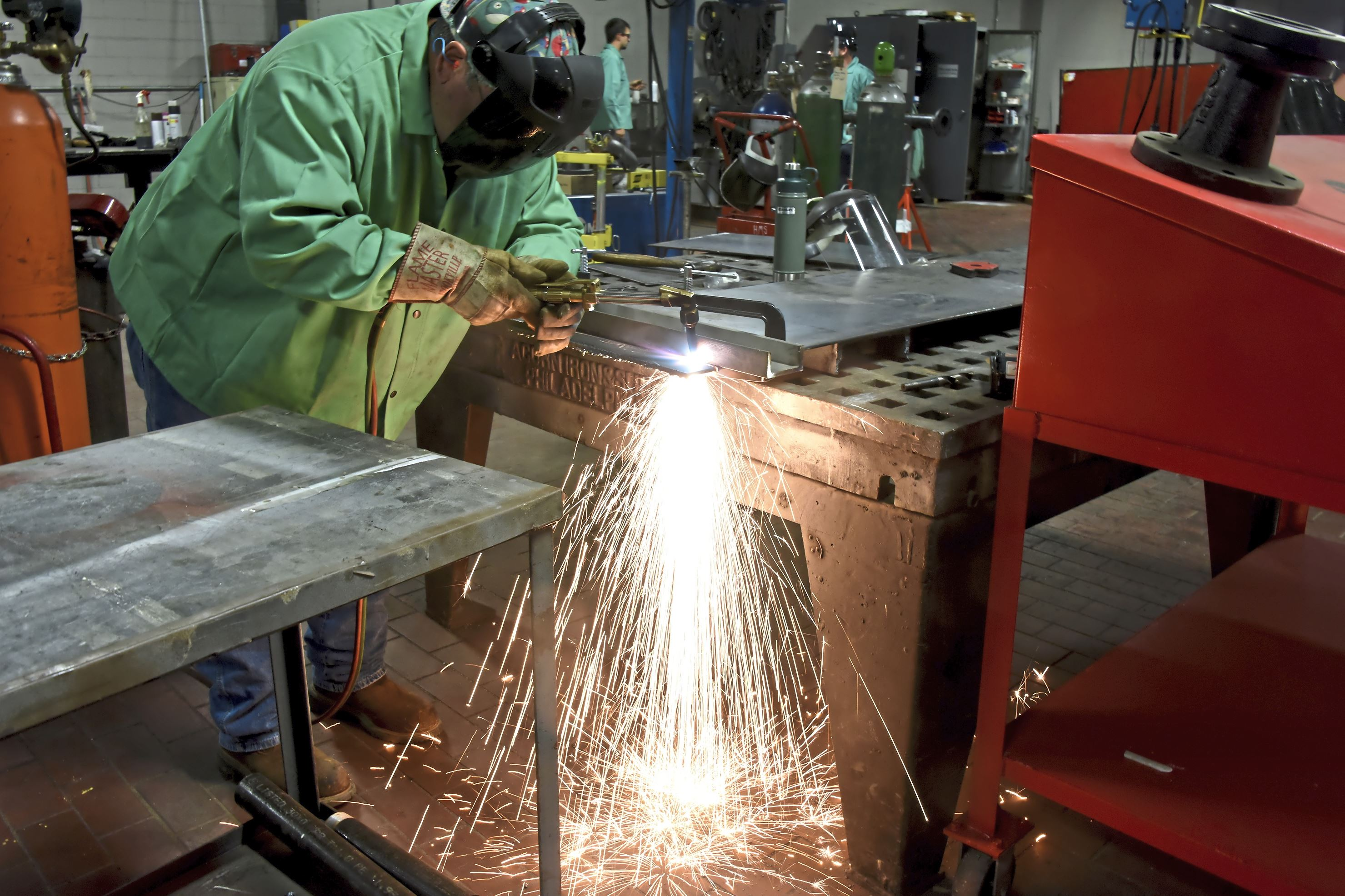 20170906dsCleanJobsBiz05 Fred Huebner , of Jefferson Hills uses a cutting torch to cut plates for boiler stands at Huckestein Mechanical Services. Inc.