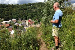 Tom Brown pauses to look at West End Village during a hike on the trail at Emerald View Park.