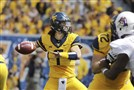 West Virginia quarterback Will Grier (7) attempts a pass the first half against against East Carolina, Saturday in Morgantown, W.Va.