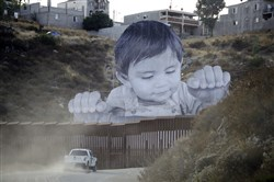 A Border Patrol vehicle drives Friday in front of a mural in Tecate, Mexico, just beyond a border structure in Tecate, Calif.