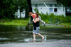 A woman wades through water with a boy near I-10 in Jacksonville, Florida as the tail end of Hurricane Irma hits, Sept. 10.