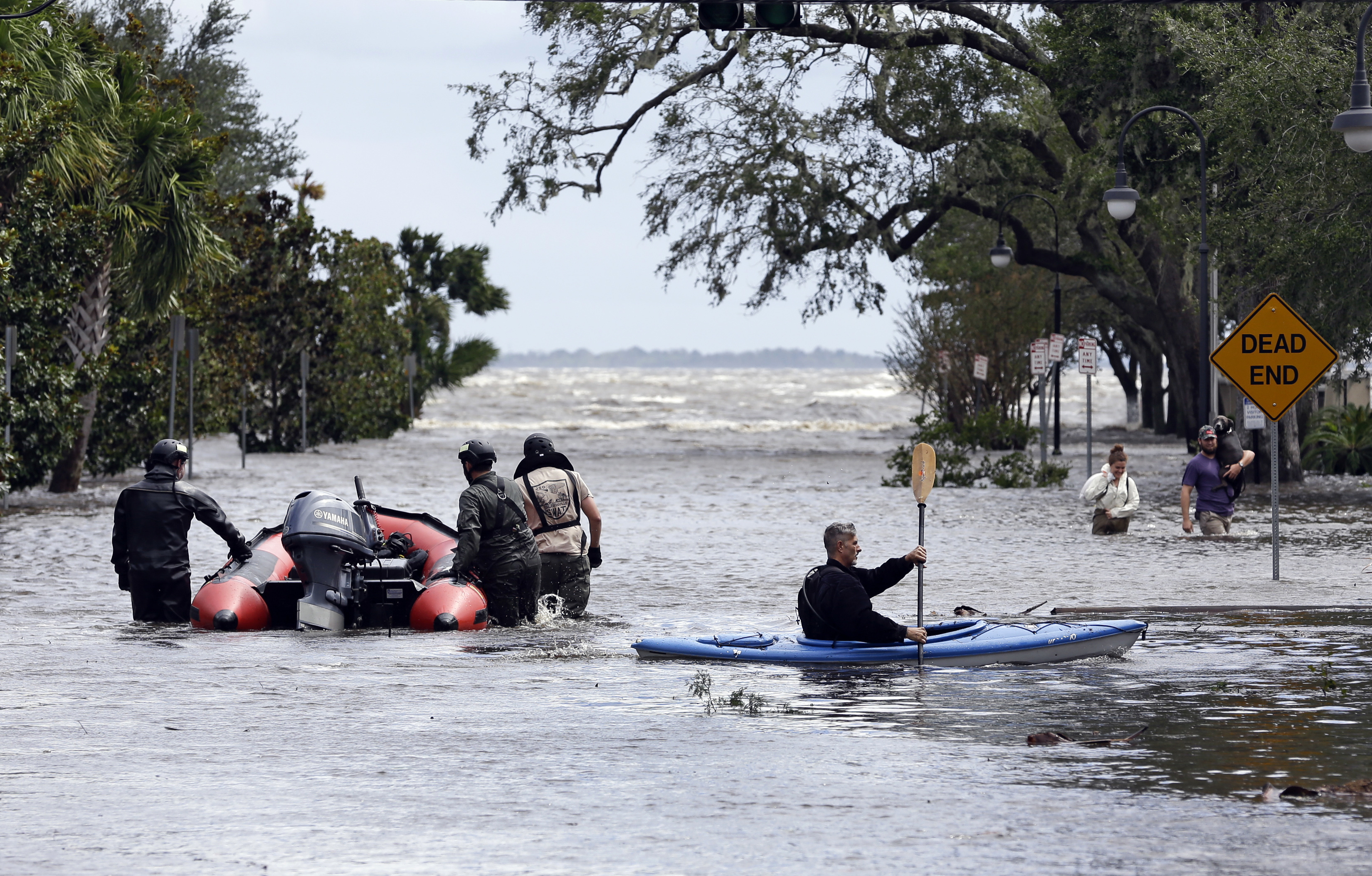 Hurricane Irma Florida Rescue workers, left, search a neighborhood for flood victims as a man on a kayak down the street after Hurricane Irma brought floodwaters to Jacksonville, Fla. Monday, Sept. 11, 2017. (AP Photo/John Raoux)