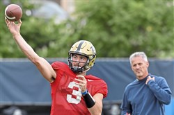 Pitt quarterback Ben DiNucci delivers a pass in front of offensive coordinator Shawn Watson during practice Tuesday.
