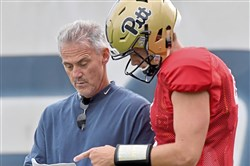 Pitt quarterback Max Browne talks with offensive coordinator Shawn Watson during practice Tuesday on the South Side.
