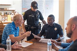 Pittsburgh Police Neighborhood Resource Officer Gabriel Figueroa, standing, and Officer Derek Payton, center right, talk to concerned resident Rich Ferro, 68, of Deutchtown.