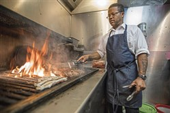 Grill master Courtney McFarlane grills burgers in the kitchen at Tessaro's in Bloomfield.