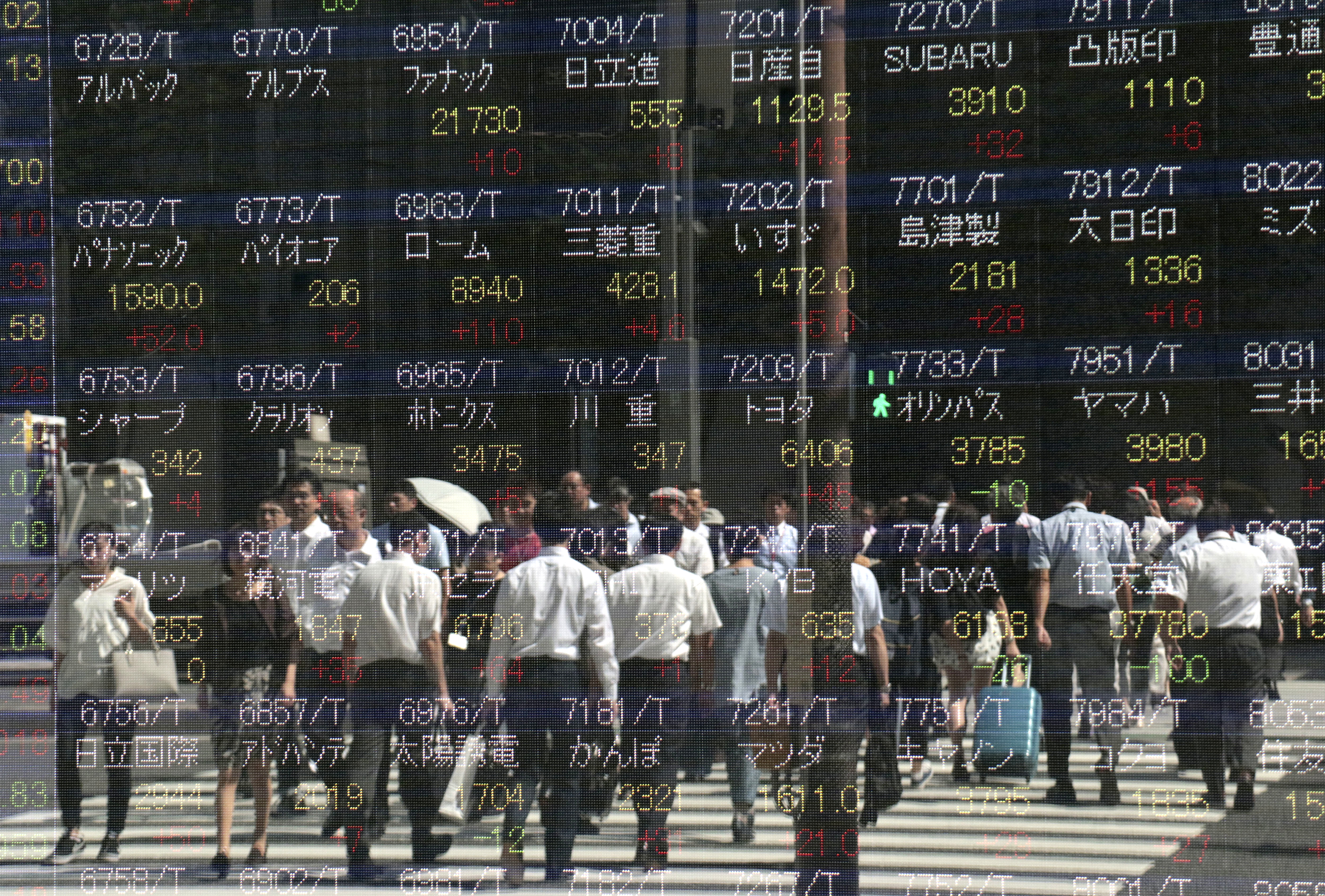 Japan Financial Markets-2 People are reflected on an electronic stock indicator of a securities firm in Tokyo, Wednesday, Sept. 13, 2017. Most Asian stock markets were higher Wednesday after U.S. shares rose on encouraging jobs data while worries about North Korea and twin hurricane disasters eased. (AP Photo/Shizuo Kambayashi)