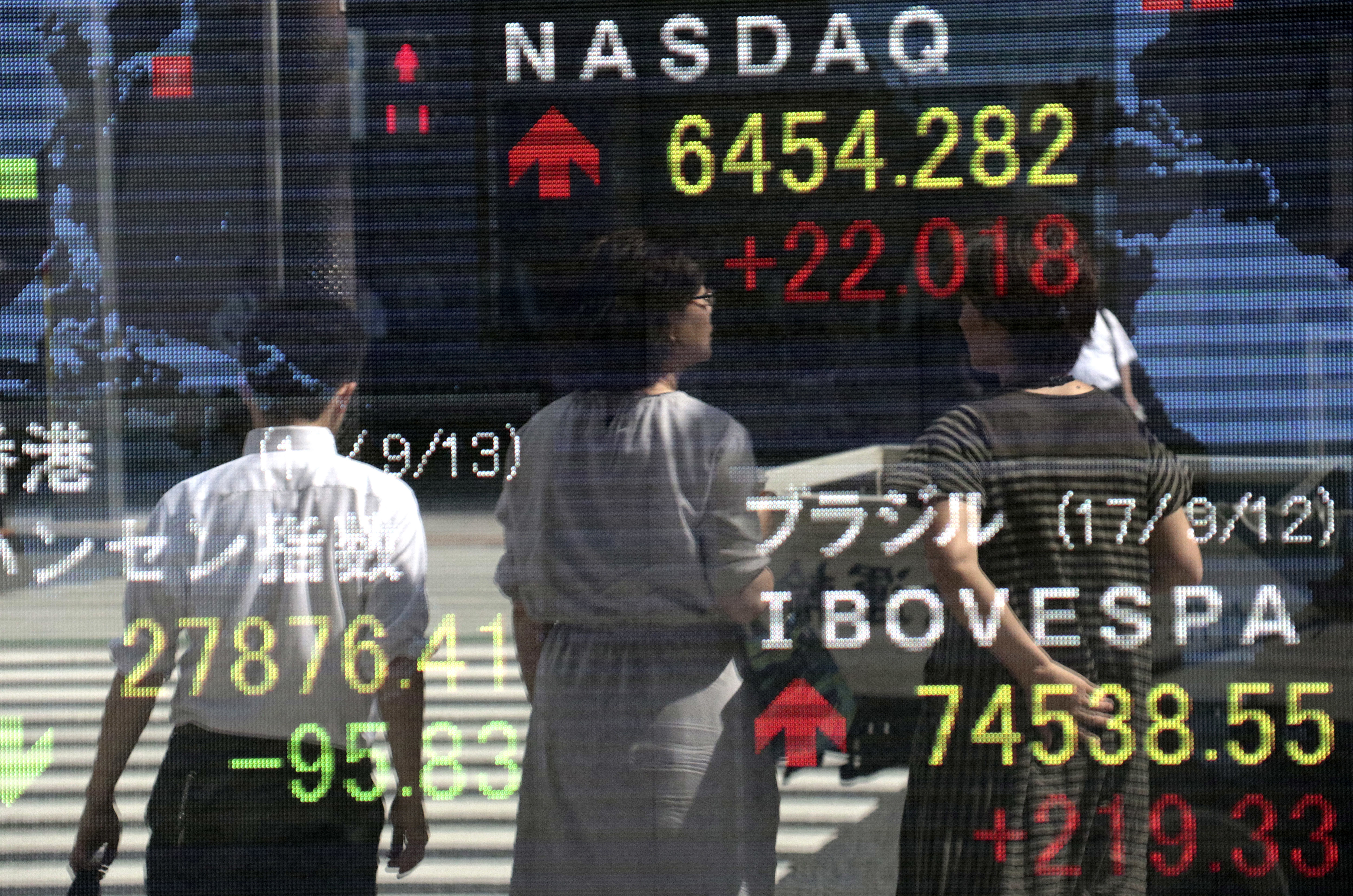Japan Financial Markets People are reflected on an electronic stock indicator of a securities firm in Tokyo, Wednesday, Sept. 13, 2017. Most Asian stock markets were higher Wednesday after U.S. shares rose on encouraging jobs data while worries about North Korea and twin hurricane disasters eased. (AP Photo/Shizuo Kambayashi)