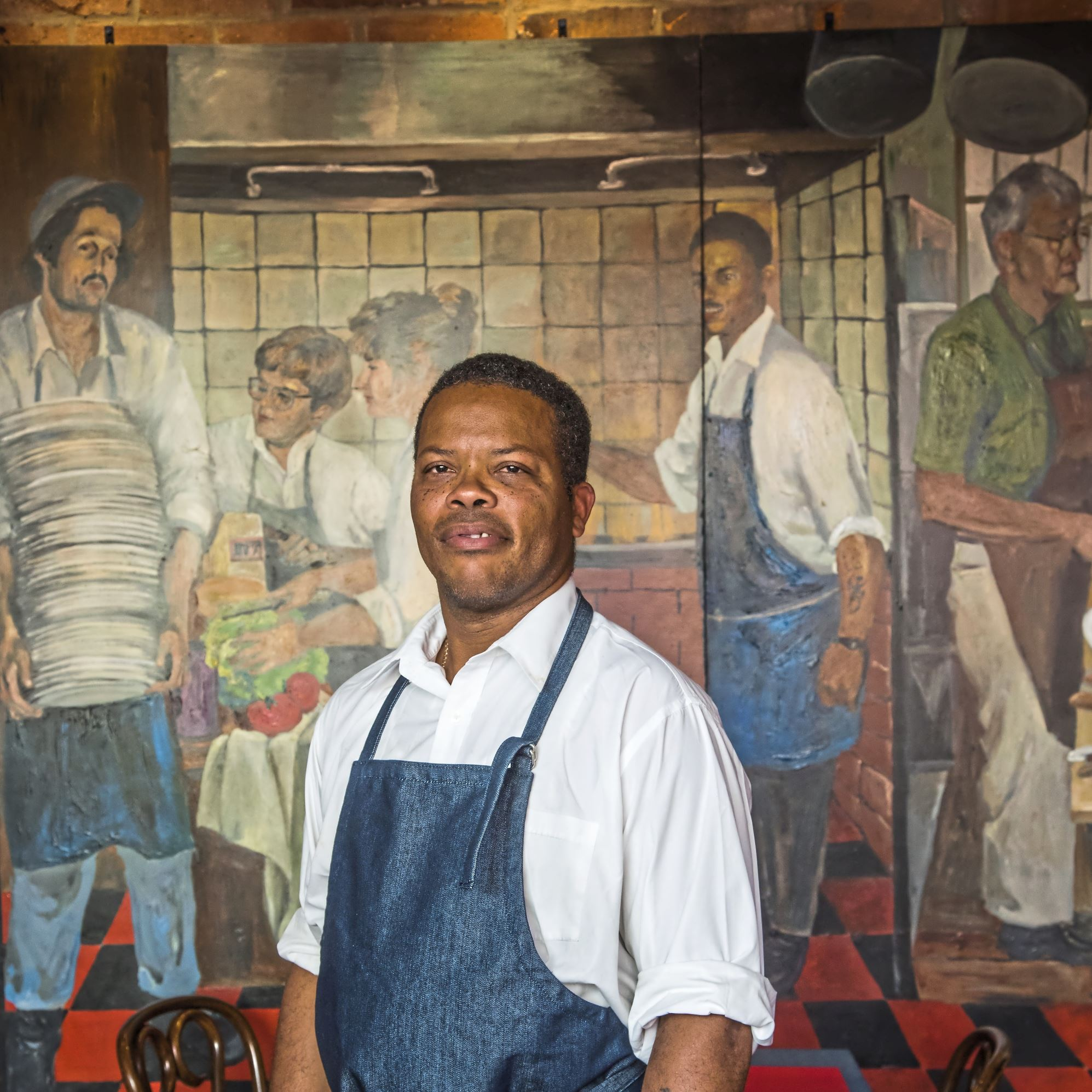 20170907arTessaros04-3 Grill master Courtney McFarlane in front of the mural at Tessaro's that features him and other members of the restaurant family.