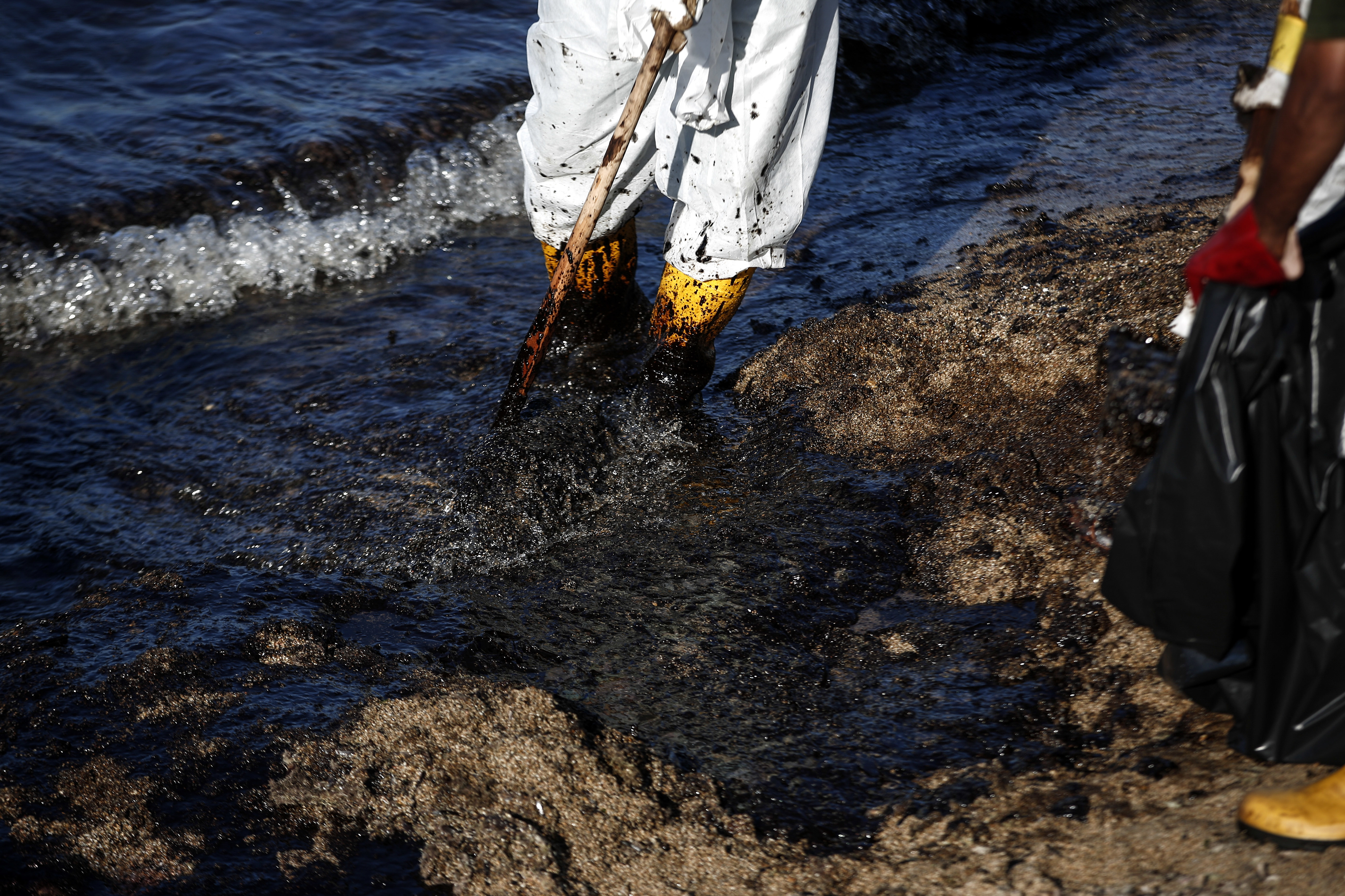 Greece Oli Spill-2 Workers clean a beach of an oil spillage at Faliro suburb, near Athens, on Thursday,Sept. 14, 2017. Greek authorities insist they are doing everything they can to clean up pollution caused by an oil spill following the sinking of a small oil tanker that has left large sections of the Greek capital's coastal areas coated in viscous, foul-smelling oil. (AP Photo/Yorgos Karahalis)