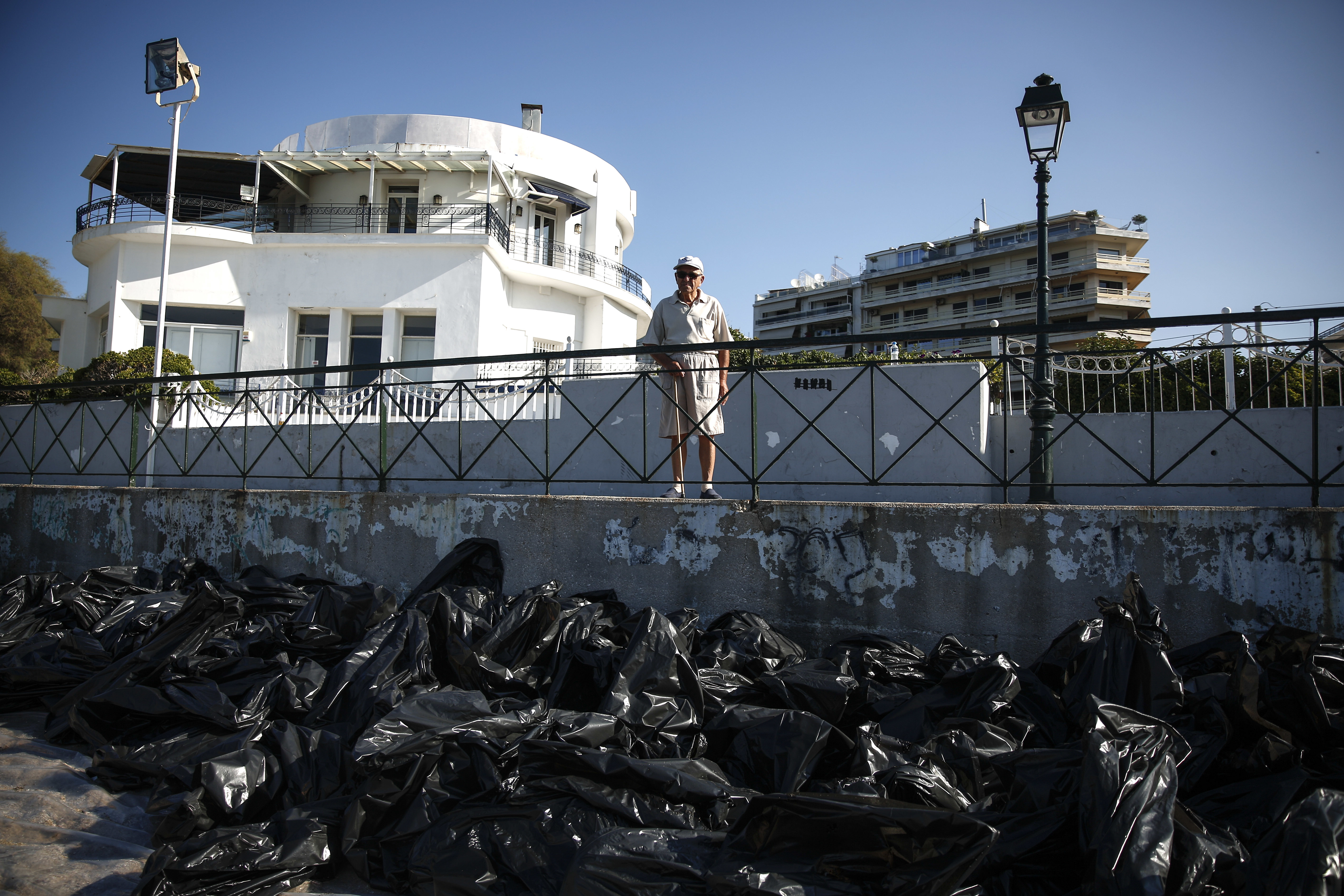Greece Oli Spill-3 A man stands over garbage bags at a beach where workers clean an oil spillage at Faliro suburb, near Athens, on Thursday,Sept. 14, 2017. Greek authorities insist they are doing everything they can to clean up pollution caused by an oil spill following the sinking of a small oil tanker that has left large sections of the Greek capital's coastal areas coated in viscous, foul-smelling oil. (AP Photo/Yorgos Karahalis)