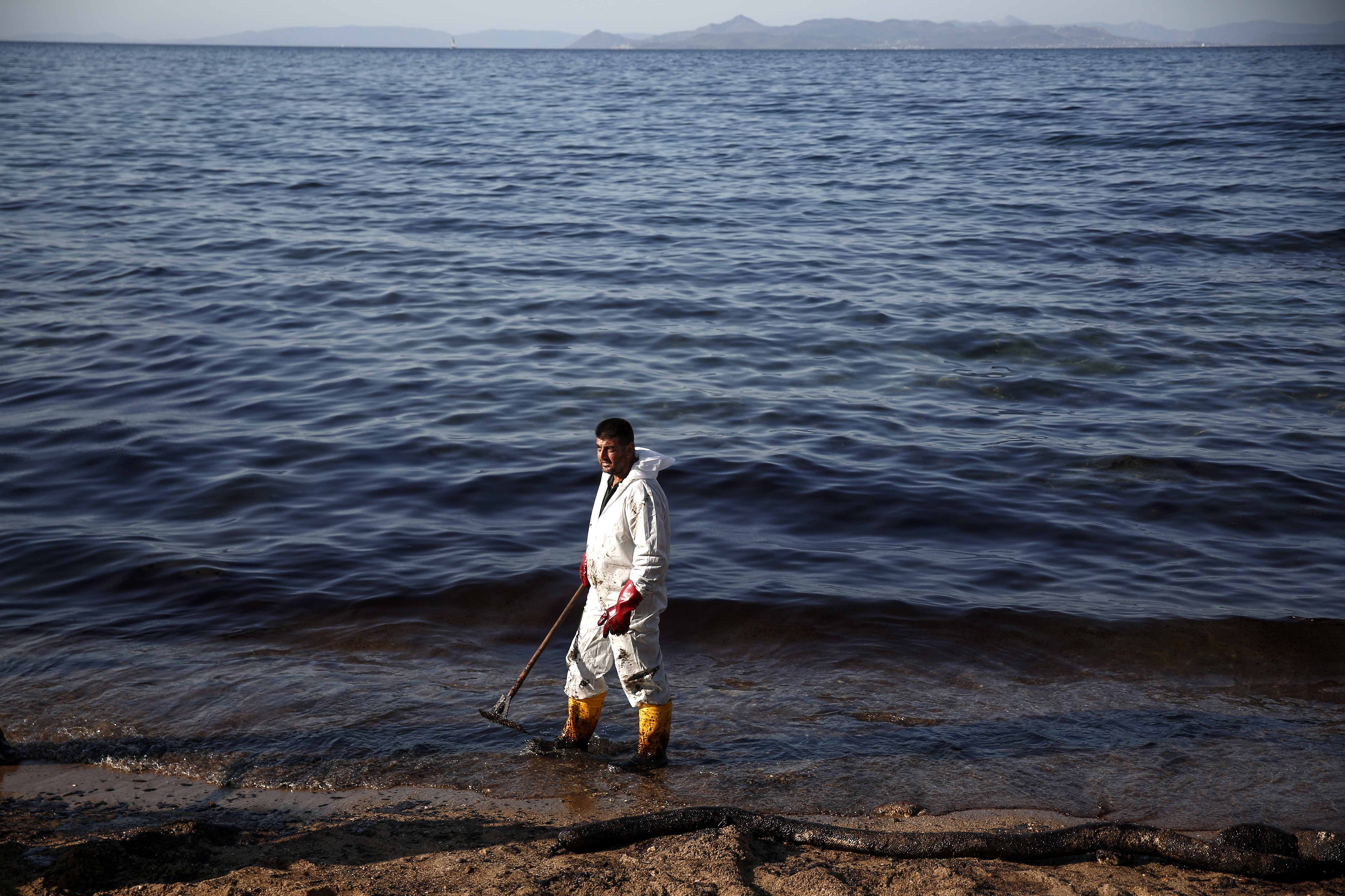 Greece Oli Spill-6 A worker cleans a beach of an oil spillage at Faliro suburb, near Athens, on Thursday,Sept. 14, 2017. Greek authorities insist they are doing everything they can to clean up pollution caused by an oil spill following the sinking of a small oil tanker that has left large sections of the Greek capital's coastal areas coated in viscous, foul-smelling oil. (AP Photo/Yorgos Karahalis)