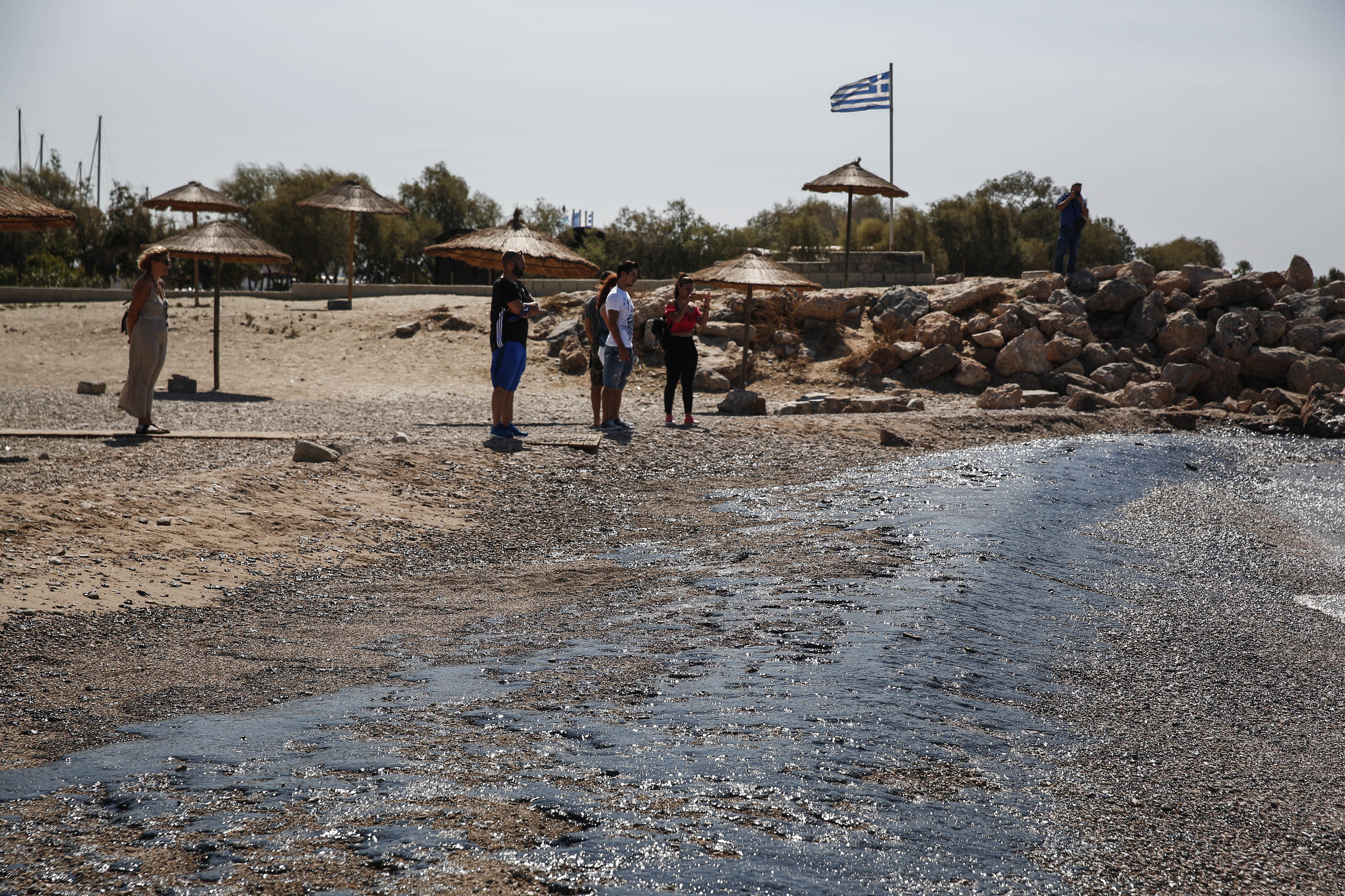 Greece Oli Spill-8 People stand on a beach where an oil spillage has been washed-up at Glyfada suburb, near Athens, on Thursday,Sept. 14, 2017. Greek authorities insist they are doing everything they can to clean up pollution caused by an oil spill following the sinking of a small oil tanker that has left large sections of the Greek capital's coastal areas coated in viscous, foul-smelling oil. (AP Photo/Yorgos Karahalis)