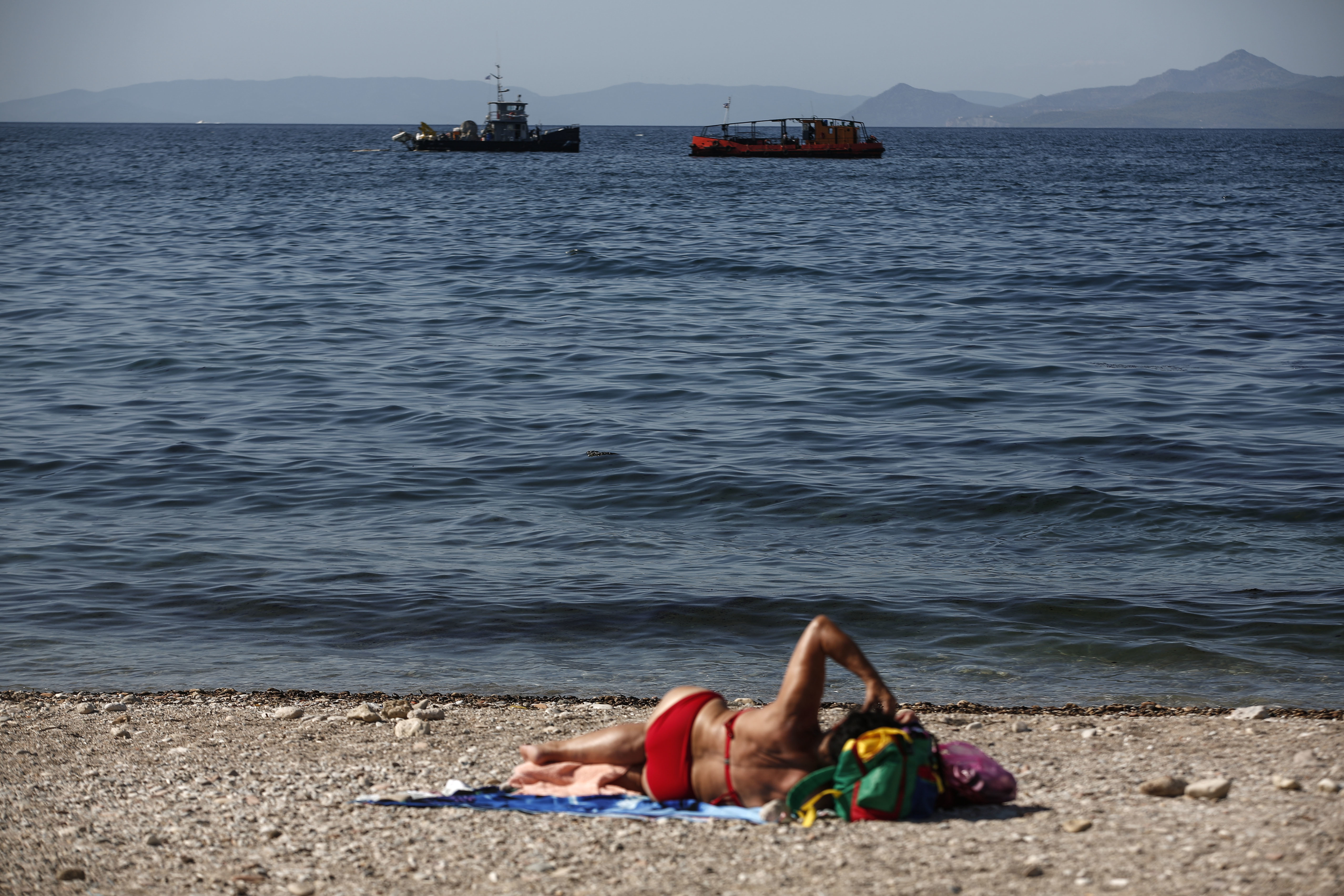 Greece Oli Spill-9 A woman sunbathes as anti-pollution vessels clean the sea from an oil spillage at Faliro suburb, near Athens, on Thursday, Sept. 14, 2017. Greek authorities insist they are doing everything they can to clean up pollution caused by an oil spill following the sinking of a small oil tanker that has left large sections of the Greek capital's coastal areas coated in viscous, foul-smelling oil. (AP Photo/Yorgos Karahalis)