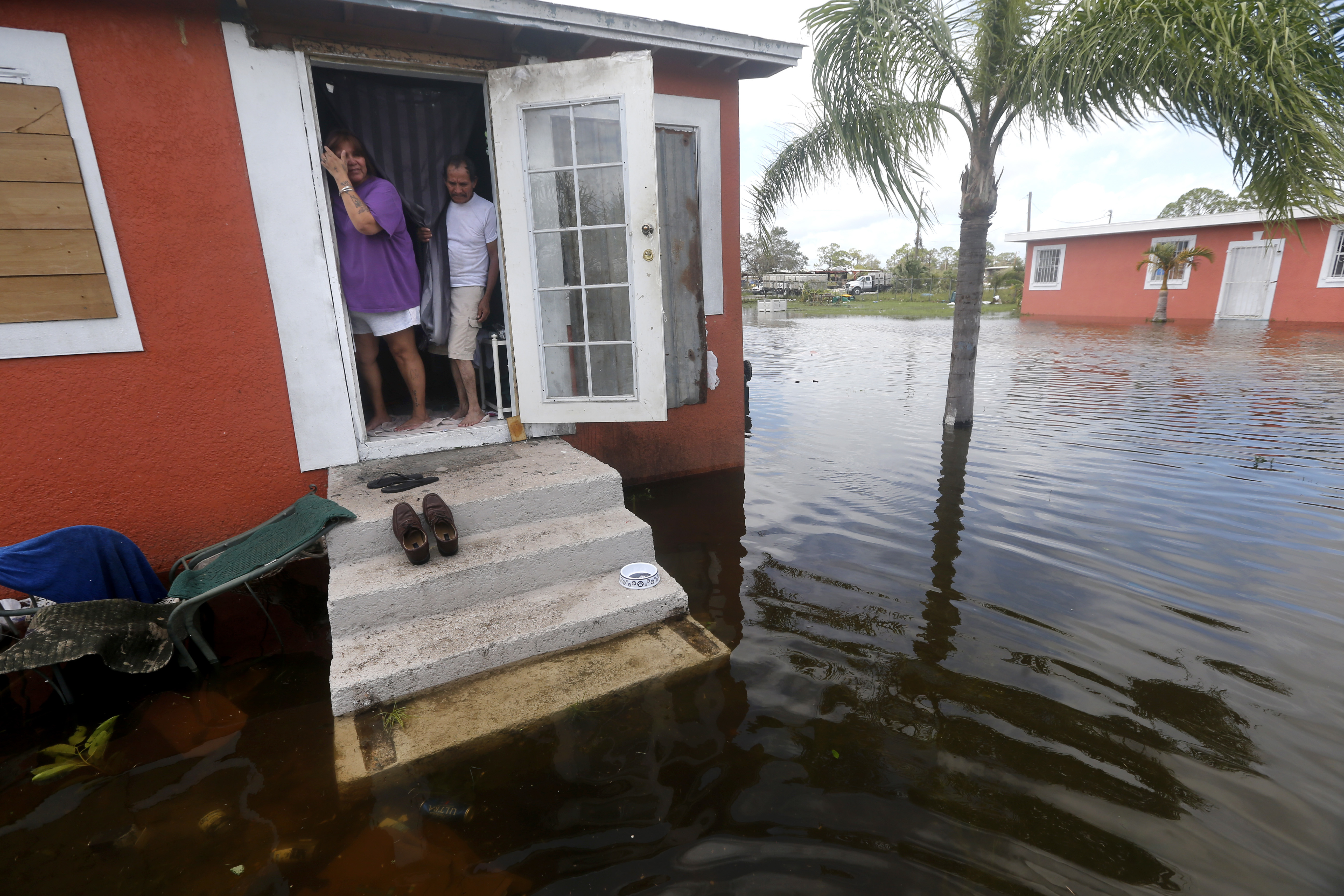 Irma The Poor-1 In this Sept. 11, 2017 file photo, Quintana and Liz Perez look at the flooding outside their home in the aftermath of Hurricane Irma, in Immokalee, Fla, one of the poorest towns in the state. Home of many day laborers and migrant workers, Immokalee sustained heavy damage from Irma that will take months to overcome. (AP Photo/Gerald Herbert)