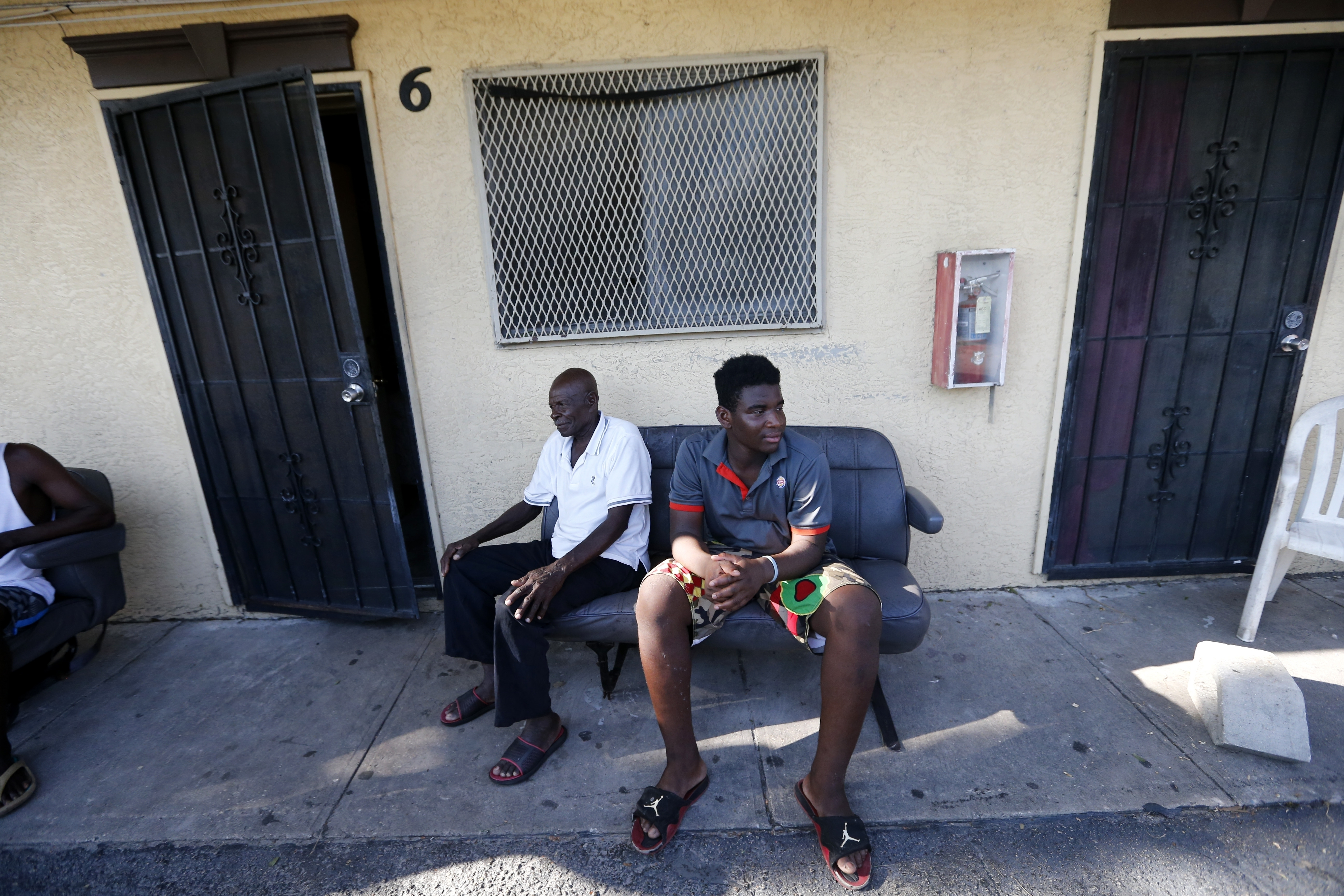 Irma The Poor-10 In this Sept. 12, 2017 photo, Woodchy Darius, right, sits outside the small cinderblock apartment he lives in, in the aftermath of Hurricane Irma, in Immokalee, Fla. A Haitian immigrant, he is trying to decide to go to school next week, or work in the fields to make up for lost income due to the storm. (AP Photo/Gerald Herbert)