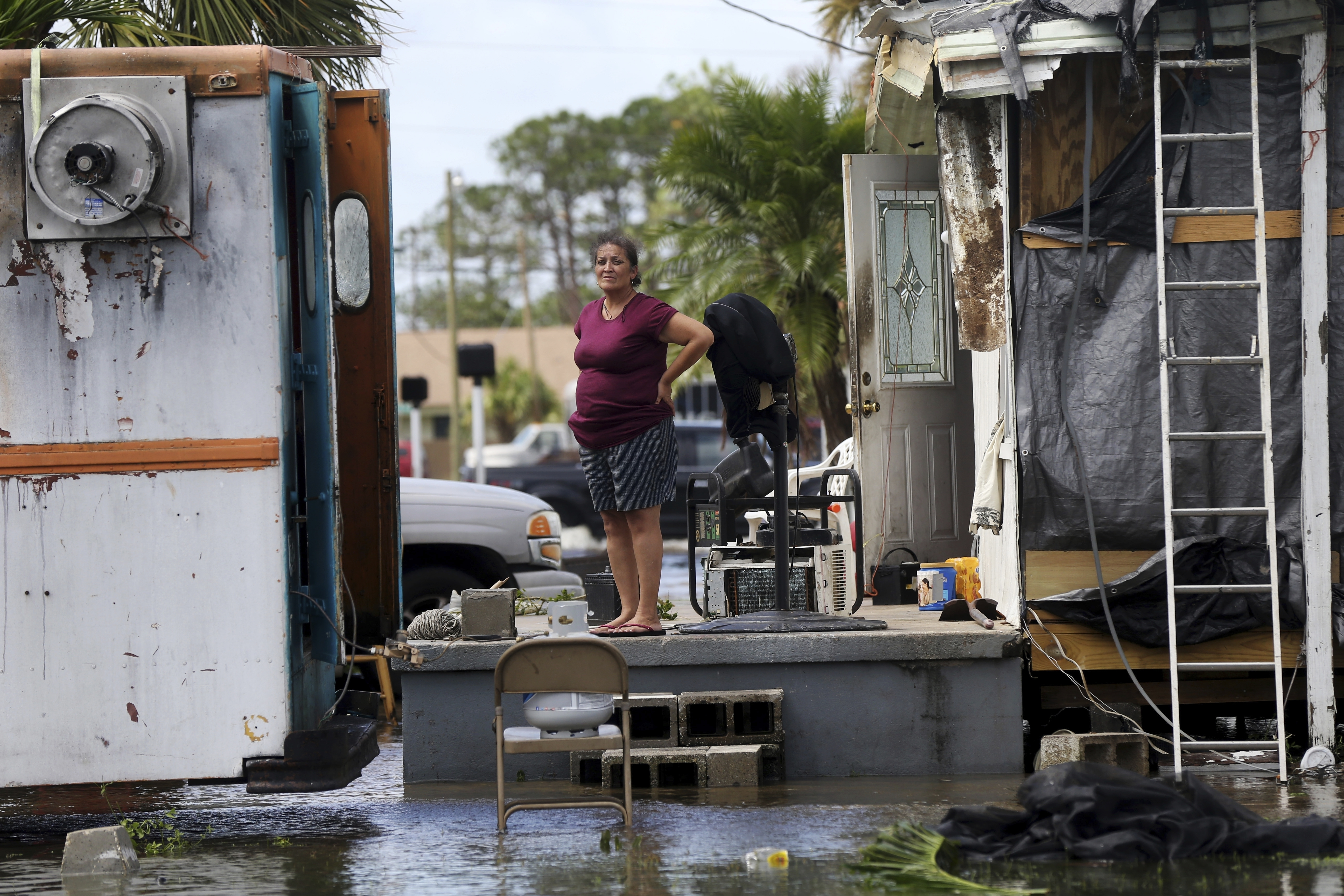 Irma The Poor-2 In this Sept. 11, 2017 file photo, Elida Dimas looks at floodwaters from her porch, in the aftermath of Hurricane Irma, in Immokalee, Fla. Irma badly damaged Dimas' mobile home and destroyed another she and her husband used for rental income, making their tough life even harder. (AP Photo/Gerald Herbert)