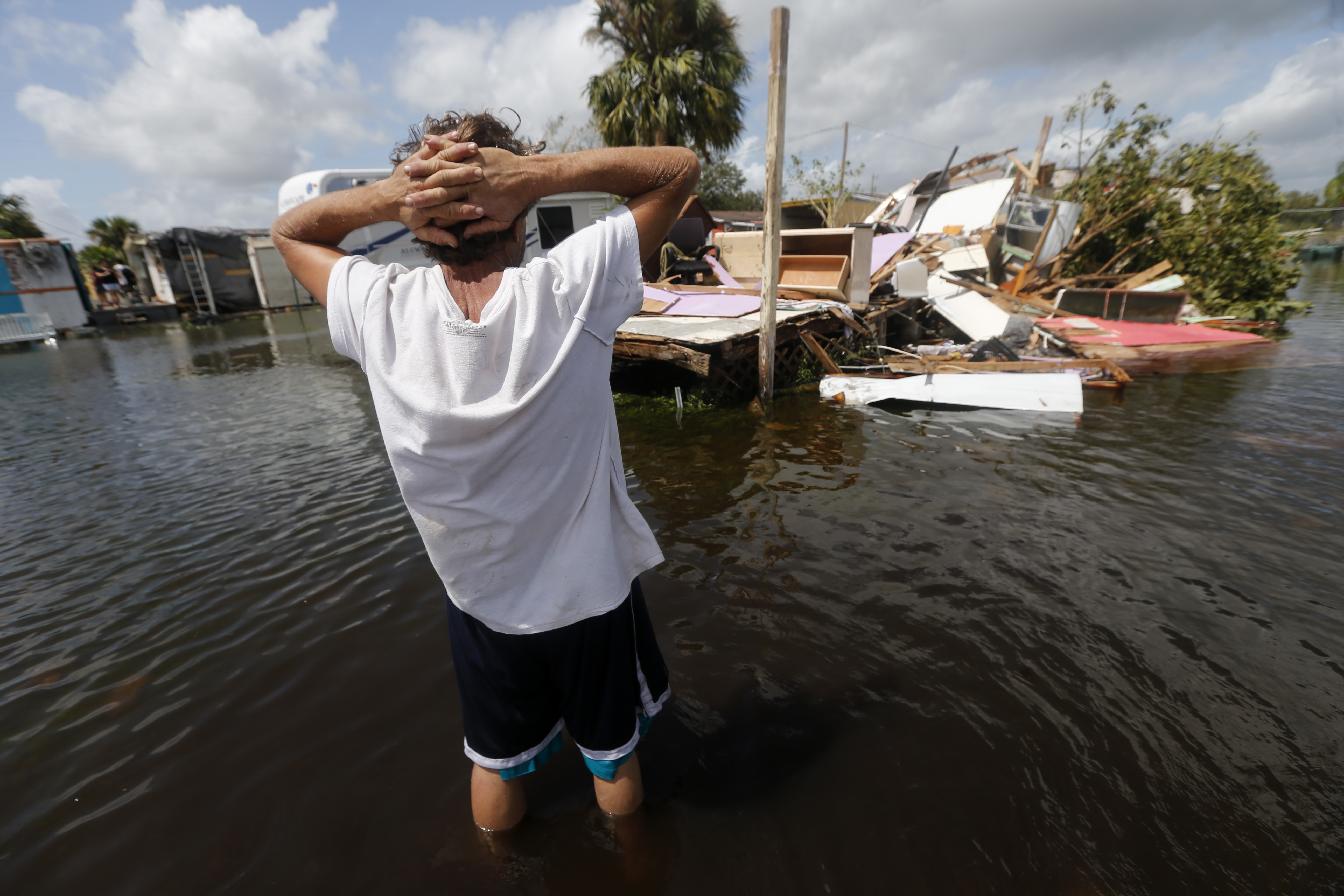 Irma The Poor-4 In this Sept. 11, 2017 photo, Larry Dimas walk around his destroyed trailer in Immokalee, Fla. Irma badly damaged Dimas' mobile home and destroyed another he used for rental income, making his tough life even harder. (AP Photo/Gerald Herbert)