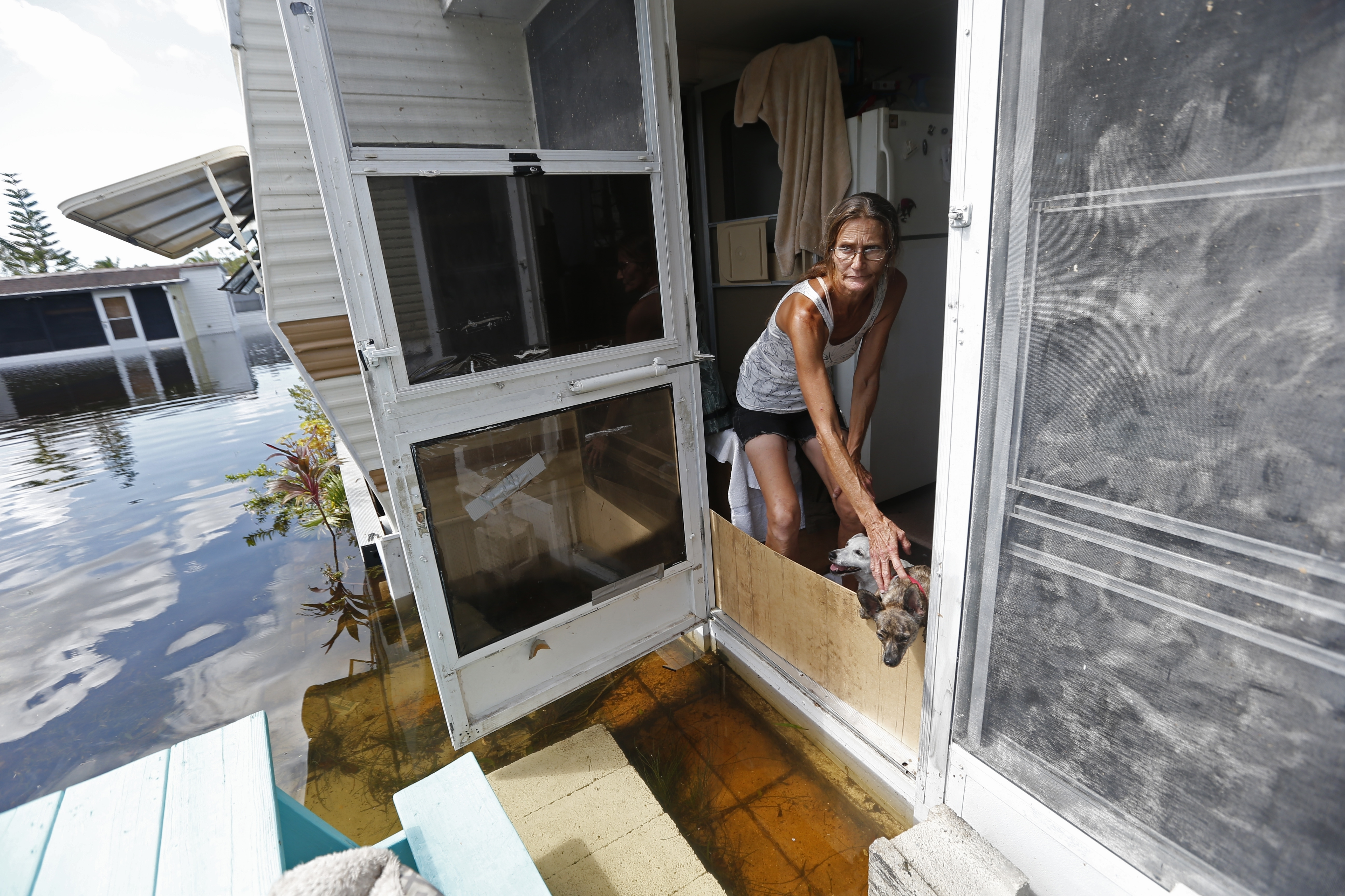 Irma The Poor-5 In this Sept. 12, 2017 photo, Cherie Ethier stands in a doorway of her mobile home with her dogs and cats, surrounded by floodwater, in the Marco Naples RV Resort, in the aftermath of Hurricane Irma, in Naples, Fla. Ethier and her husband stayed in a hotel during the storm, but returned to their trailer as soon as they could. (AP Photo/Gerald Herbert)