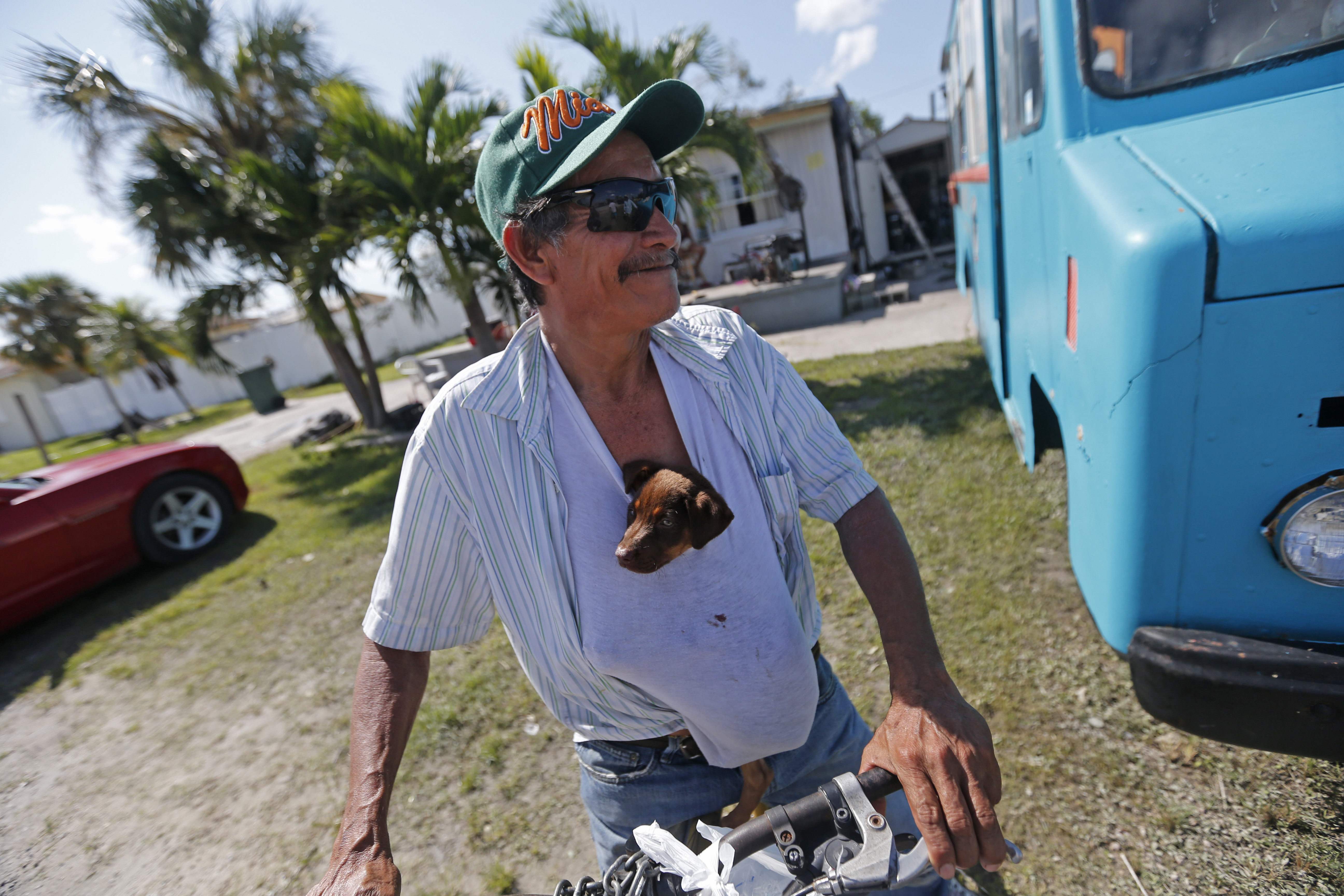 """Irma The Poor-6 In this Sept. 12, 2017 photo, Nicolas Perez keeps a puppy he named """"Irma,"""" stuffed in his shirt, who he rescued from flooding in the aftermath of Hurricane Irma, in Immokalee, Fla. The town is one of the poorest in the state. Home of many day laborers and migrant workers, Immokalee sustained heavy damage from Irma that will take months to overcome. (AP Photo/Gerald Herbert)"""