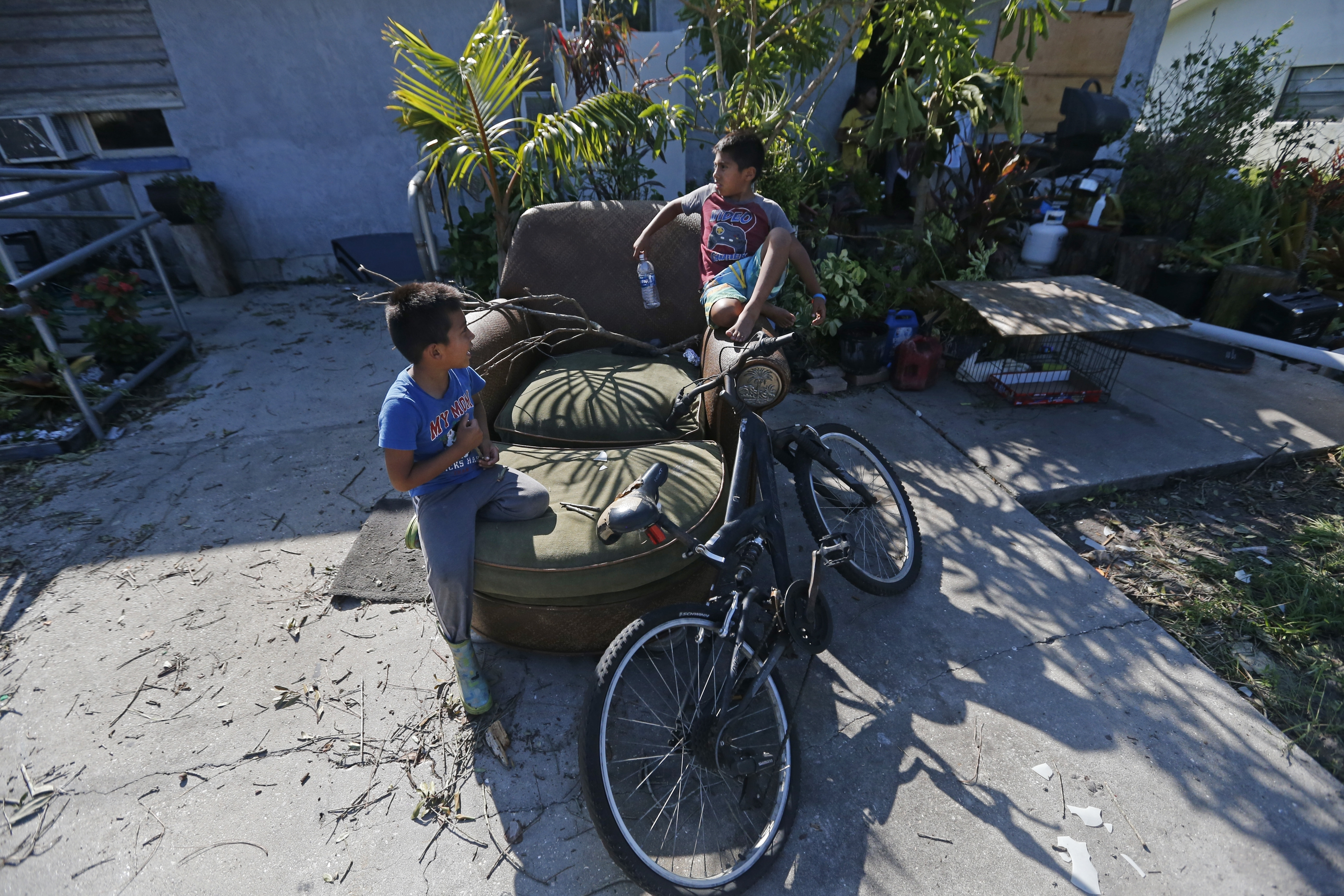 Irma The Poor-8 In this Sept. 12, 2017 photo, Giovani Gaspar, 6, right, and his brother, Isaac, 5, play on a chair outside their home, in the aftermath of Hurricane Irma, in Immokalee, Fla. Their father spent $600 getting ready for Irma, the equivalent of two weeks pay. (AP Photo/Gerald Herbert)