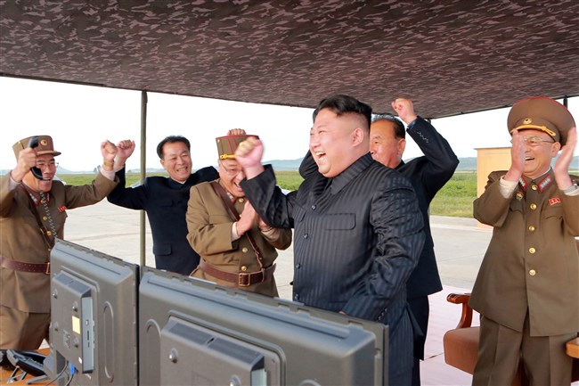 In this undated photo distributed Saturday by the North Korean government, North Korean leader Kim Jong Un, center, celebrates what was said to be the test launch of an intermediate range Hwasong-12 missile at an undisclosed location in North Korea.