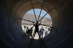 People stand in a metal tube after a test of a Hyperloop One propulsion system in North Las Vegas, Nev.