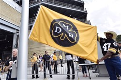 Rocky Bleier and Mel Blount raise a flag to honor Dan Rooney before Steelers take on Vikings Sunday.