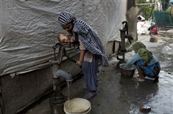 A Rohingya Muslim woman holds a child as she pumps water at a camp for refugees in New Delhi on Sept. 18.
