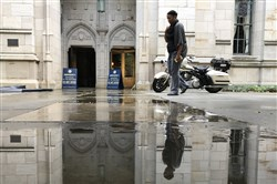A woman walks by water that spilled out of the Cathedral of Learning following a water main break inside the structure on Monday.