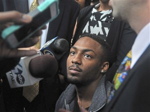 Leon Ford, center, listens to his attorneys during a press conference in October 2013.