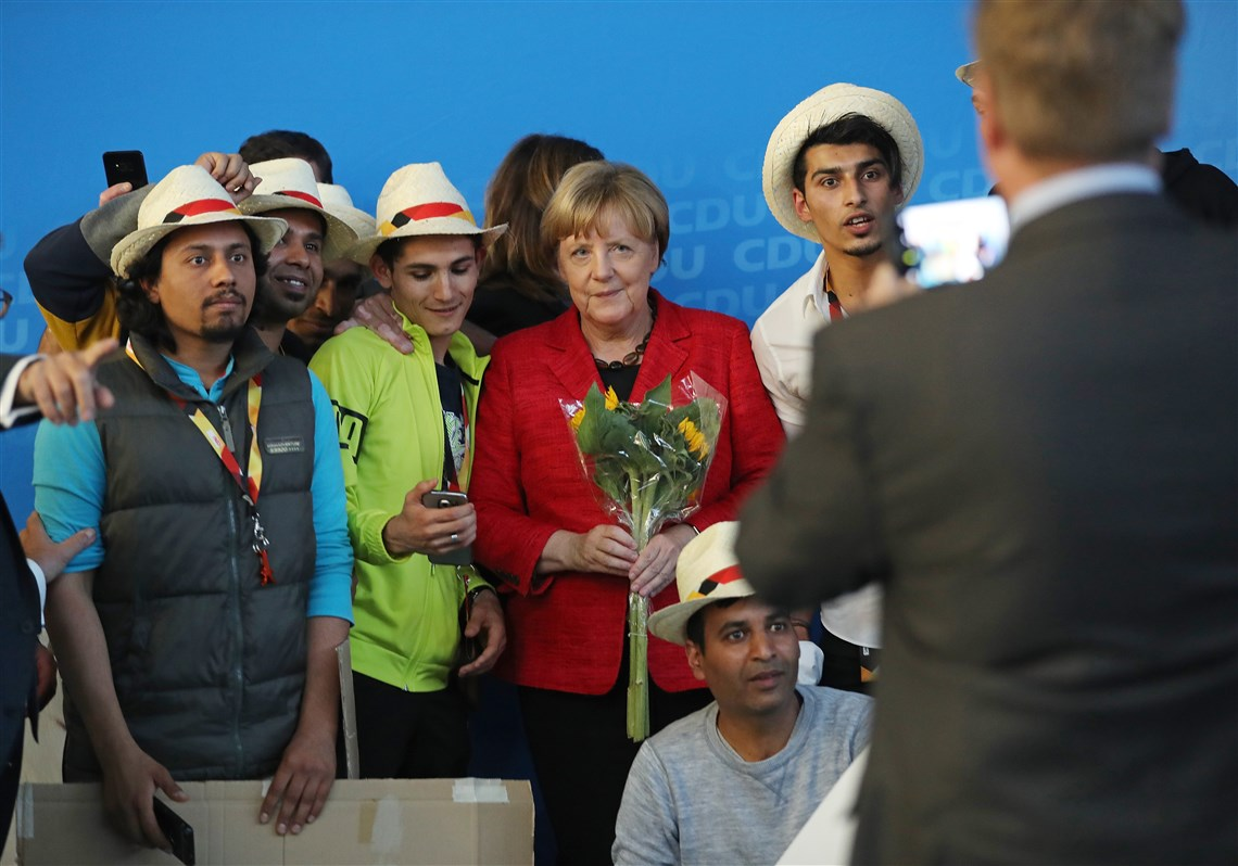 German Chancellor Angela Merkel, a Christian Democrat, poses for a photo with Syrian refugees after she spoke at an election campaign stop Sept. 19 in Schwerin, Germany.