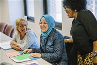Kholoud Alteara, originally from Syria, center, talks with classmates, Rosalba Lozano of Colombia, left, and Lilian Amisi from the Democratic Republic of Congo during an ESL class on September 14 Downtown.