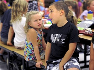 Katie Gondring and Jordan Davis, first-graders at Muse Elementary School, hang out during lunch on Thursday.