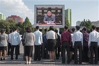 Spectators on Friday listen to a television news broadcast of a statement by North Korean leader Kim Jong Un outside the central railway station in Pyongyang.