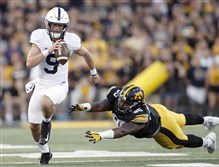 Penn State quarterback Trace McSorley runs with the ball as Iowa defensive lineman Cedrick Lattimore defends during a game in Sept. 2017 in Iowa City, Iowa. The Nittany Lions will face Washington in the Fiesta Bowl on Dec. 30.