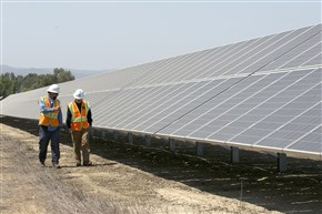 FILE - In this Aug. 17, 2017, file photo, solar tech Joshua Valdez, left, and senior plant managerTim Wisdom walk past solar panels at a Pacific Gas and Electric Solar Plant, in Dixon, Calif. Cheap solar panels imported from China and other countries have led to a boom in the U.S. solar industry, where rooftop and other installations have surged 10-fold since 2011. But two U.S. solar manufacturing companies say the flood of imports has led one to bankruptcy and forced the other to lay off three-quarters of its workforce.