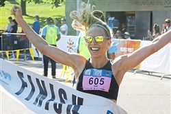 Jennifer Bigham of Squirrel Hill crosses the finish line to win the women's division of the Great Race on Sunday.