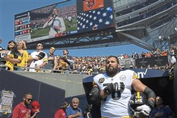 Wilbur Pauley, singing the national anthem, is visible on the scoreboard screen as Pittsburgh Steeler Alejandro Villanueva stands at the entrance of the tunnel at Soldier Field in Chicago on Sunday.